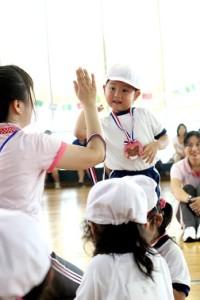 先生にメダルを掛けてもらいハイタッチする園児