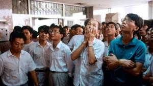 交易所の株価変動情報を眺める人々